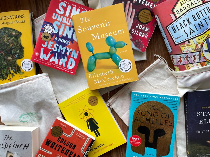 An assortment of books, including Sing, Unburied, Sing by Jesmyn Ward, The Souvenir Museum by Elizabeth McCracken, The Song of Achilles by Madeline Miller and many others.